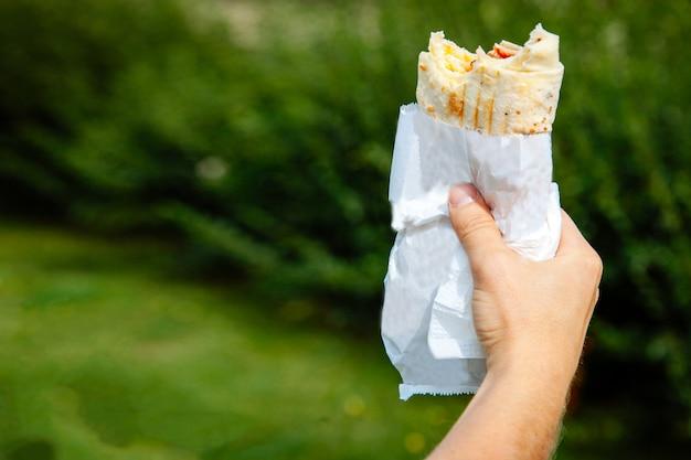 Apetyczny fast food, doner, shaurma, w opakowaniu w rękach mężczyzny na tle zielonej trawy