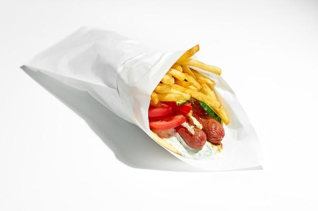 Apetyczny grecki gyros z wędzonymi kiełbaskami, pomidorami, ogórkami, frytkami w picie z jogurtem. papier do pakowania. jedzenie uliczne, twarde światło. biała powierzchnia