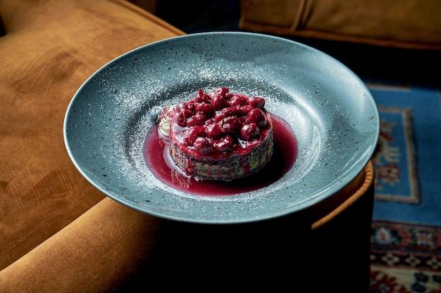 Apetyczny kawałek ciasta czekoladowego z wiśniami i dżemem, budyniem, podany na niebieskim talerzu. restauracja serwująca deser