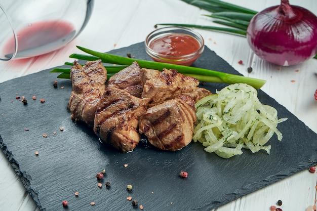 Apetyczny kebab wołowy z przyprawami i cebulą na czarnej łupkowej tacy na białym tle. shahlik. zamknąć porcję mięsa z grilla