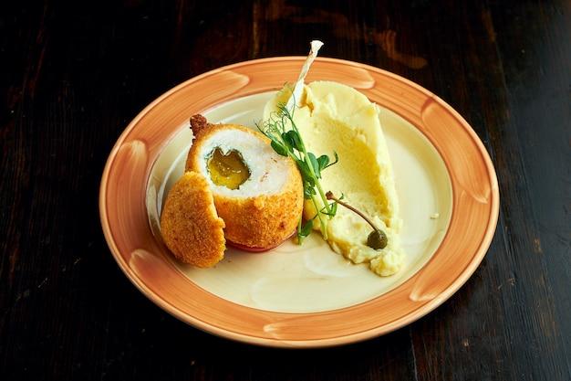 Apetyczny kotlet kijowski w bułce tartej z masłem i ziołami, podawany z puree ziemniaczanym w talerzu na ciemnym tle. chicken kyiv