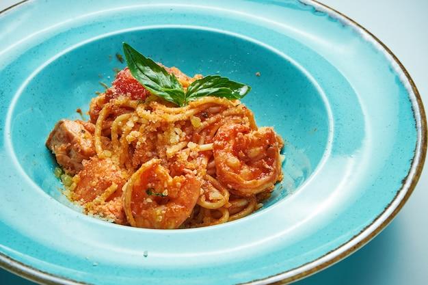 Apetyczny makaron z pomidorami i krewetkami, parmezanem w niebieskiej misce na szarej powierzchni. kuchnia włoska