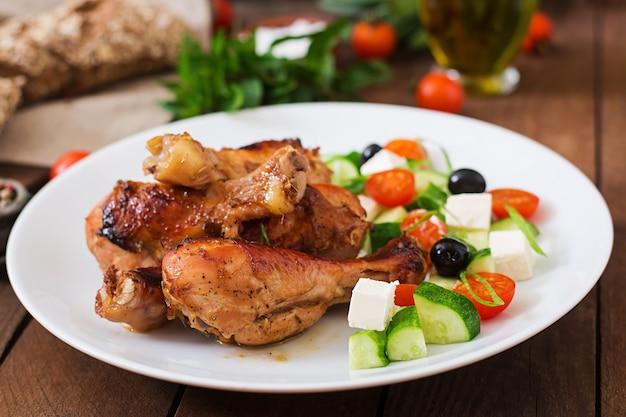 Apetyczny piec pieczone złote udka z kurczaka i sałatka grecka