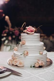 Apetyczny piękny, wielowarstwowy słodki tort weselny pokryty białym kremowym kwiatem deserowym