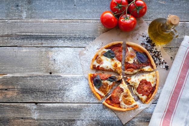 Apetyczny pizza margarita na drewnianym stole.