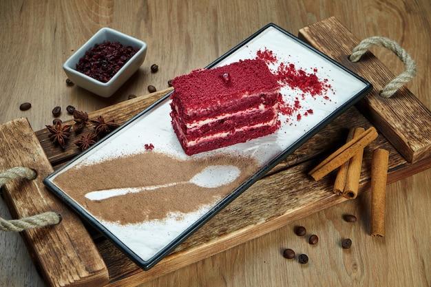 Apetyczny plasterek ciasta biszkoptowego z białą śmietaną i czerwonymi babeczkami. smaczny deser na kawę. ciasto z czerwonego aksamitu. zdjęcie żywności leżało płasko. piekarnia