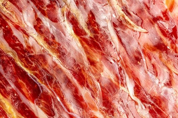 Apetyczny plastry szynki iberyjskiej na pierwszym planie jako tekstury. surowe mięso, które dzięki procesowi surowego solenia i naturalnego peklowania staje się wytworem wysokiej kuchni i luksusu gastronomicznego.