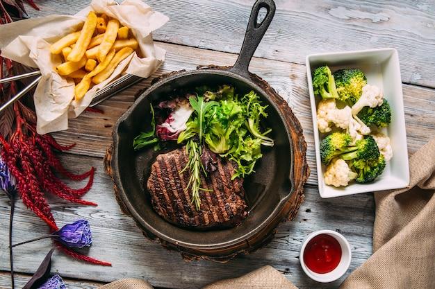 Apetyczny soczysty stek wołowy z zieleniną na patelni
