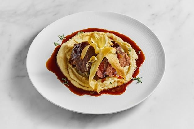 Apetyczny stek z policzka bawola przyozdobiony puree ziemniaczanym i czerwonym sosem, podawany na białym talerzu na marmurowej powierzchni
