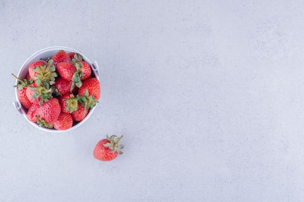 Apetyczny stos truskawek w małym wiaderku na marmurowym tle. zdjęcie wysokiej jakości