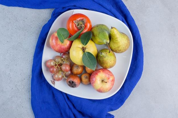 Apetyczny talerz asortymentu owoców na niebieskim obrusie na tle marmuru.