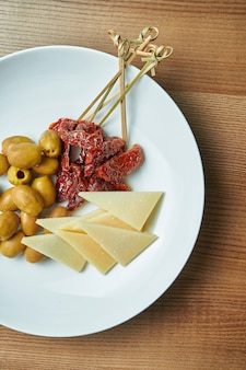 Apetyczny włoski antipasto - suszone pomidory, oliwki i parmezan w białym talerzu na drewnianym stole