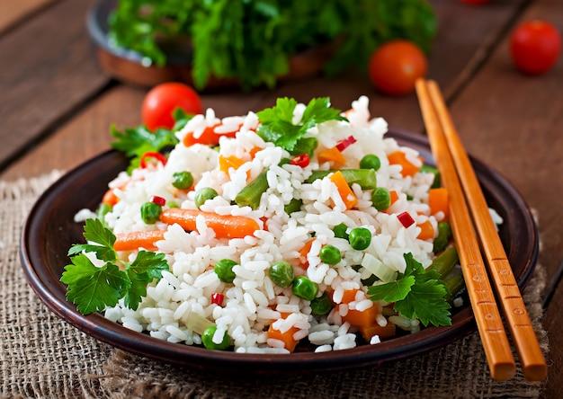 Apetyczny zdrowy ryż z warzywami w białym talerzu na drewnianym stole.