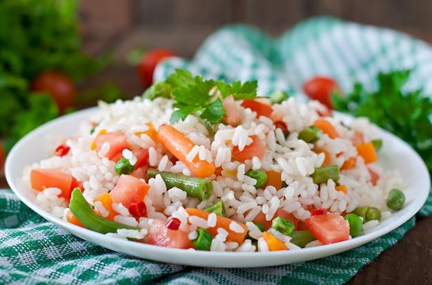 Apetyczny zdrowy ryż z warzywami w białym talerzu na drewnianym stole