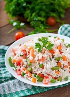 Apetyczny zdrowy ryż z warzywami w białym talerzu na drewnianym