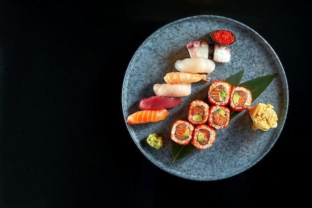 Apetyczny zestaw sushi składający się z różnych nigiri i uramaki z łososiem, awokado i kawiorem tobiko. japońska kuchnia tradycyjna. dostawa jedzenia. pojedynczo na czarno