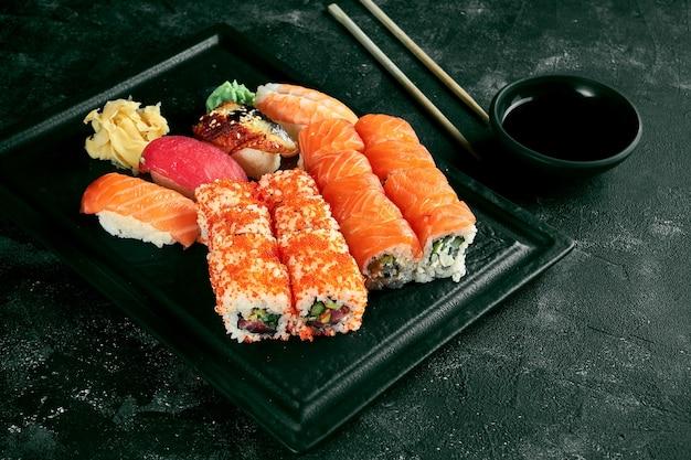 Apetyczny zestaw sushi składający się z różnych uramaki z łososiem, awokado i kawiorem tobiko oraz nigiri. japońska kuchnia tradycyjna. dostawa jedzenia. czarne tło