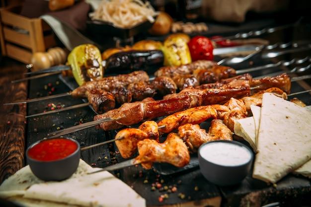 Apetyczny zestaw szaszłyków kebabowych na ciemnej drewnianej powierzchni