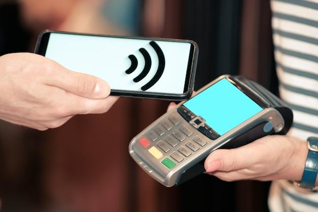 Aplikacja w smartfonie do płatności za towar online, w terminalu płatniczym. pieniądz elektroniczny. bankowość mobilna. kompleks handlowy.