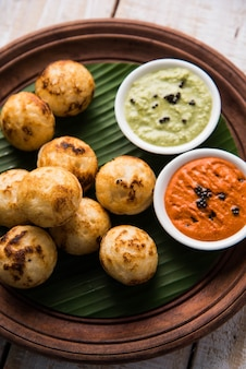 Appam lub mixed dal lub rava appe podawane na nastrojowym tle z zielonym i czerwonym sosem chutney. kula w kształcie popularnej południowoindyjskiej receptury śniadaniowej. selektywne skupienie