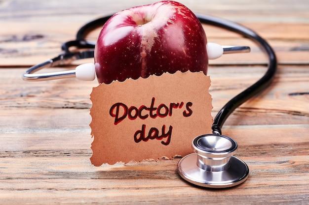 Apple, stetoskop i kartkę z życzeniami. gratulacje z okazji wakacji lekarskich.