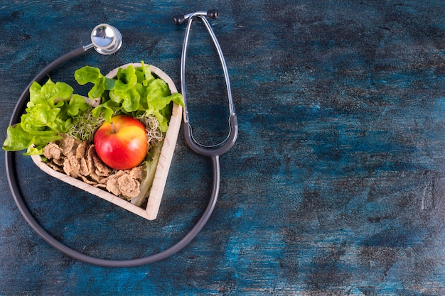 Apple z sałatą i zbożami w drewnianym sercu
