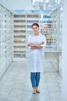 Apteka. poważna kobieta w białym płaszczu z założonymi rękami na piersi, stojąca w holu apteki
