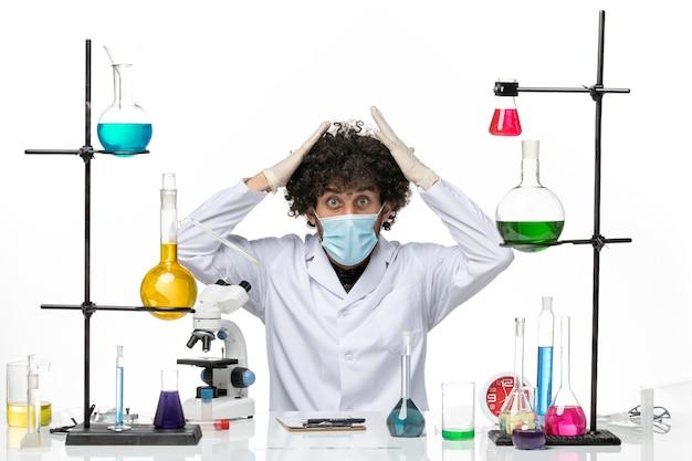 Aptekarz mężczyzna w garniturze medycznym z maską, siedzący z różnymi roztworami na jasnej, białej przestrzeni