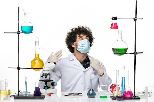 Aptekarz mężczyzna w garniturze medycznym z maską, siedzący z roztworami na jasnej, białej przestrzeni