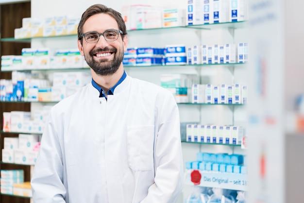 Aptekarz w aptece stojącej na półce z lekami