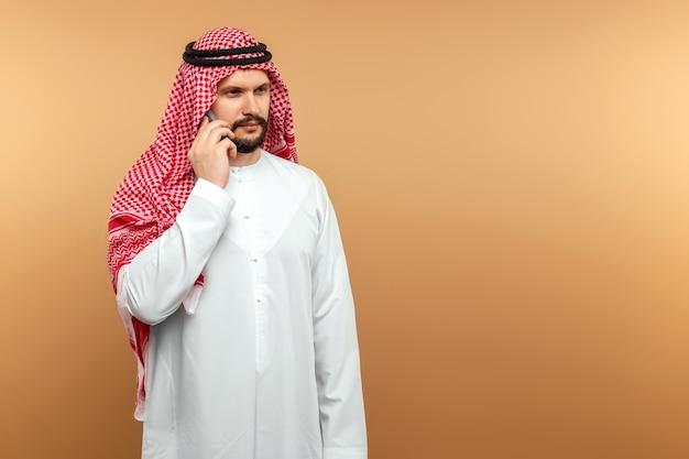 Arab człowiek biznesmen w krajowych ubrania rozmawia na smartfonie, jak beżowa ściana.