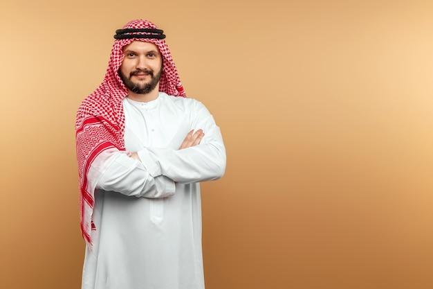 Arab człowiek biznesmen w krajowych ubrania założył ręce na piersi, beżowa ściana.