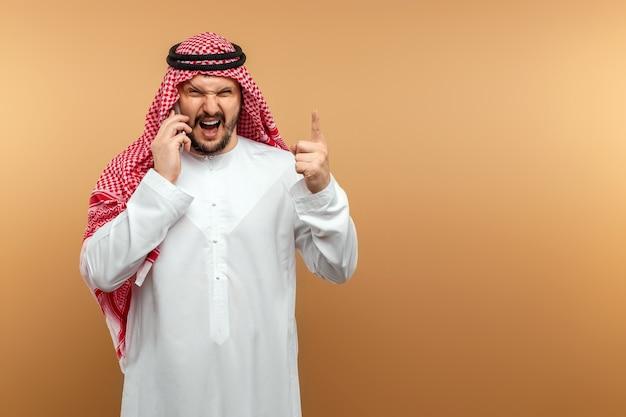 Arab człowiek biznesmen w krajowych ubraniach krzyczy niezadowolony int. odbiornik smartfona. biznes na bliskim wschodzie
