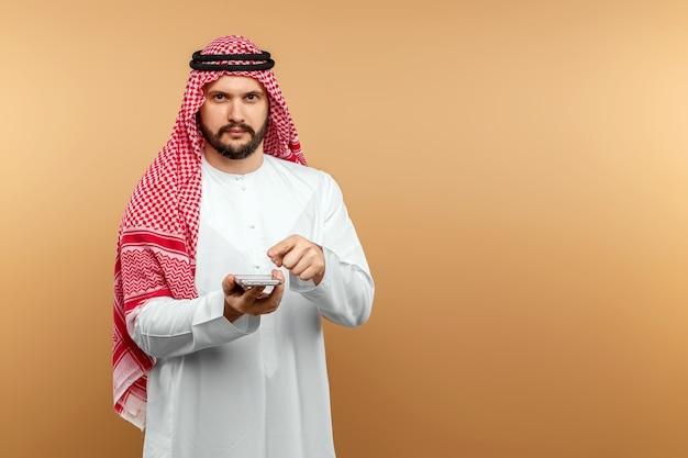 Arab człowiek biznesmen w stroju narodowego trzyma smartfon w dłoniach, beżowa ściana.