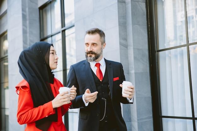 Arab muzułmańscy biznesmeni mężczyzna i kobieta poranna kawa spacerująca rozmowa