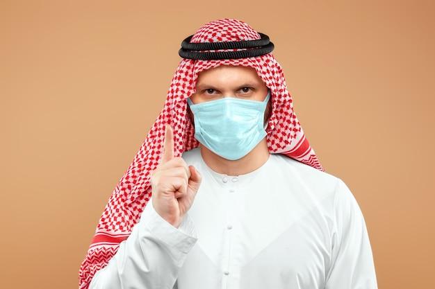 Arab w masce trzyma probówkę w stroju ludowym.