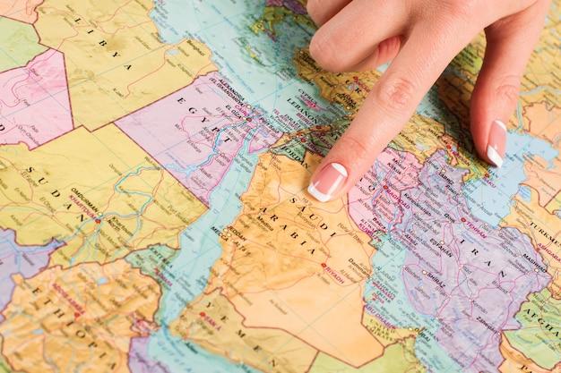 Arabia saudyjska na mapie świata. kobiecy palec wskazujący na mapie. studiowanie krajów wschodnich. największy stan regionu.