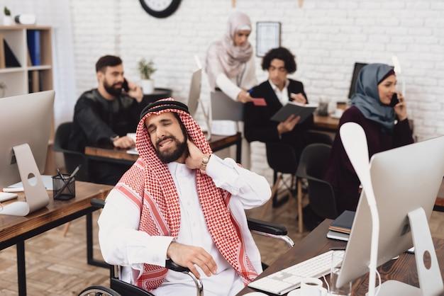 Arabia saudyjska w bólu szyi w wózku inwalidzkim w biurze.