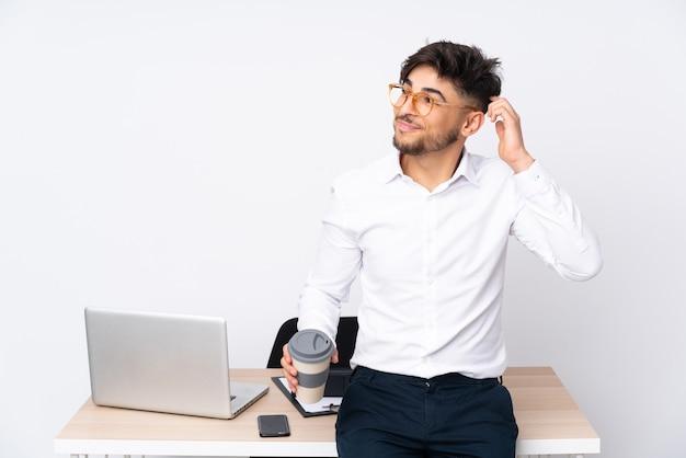 Arabian mężczyzna w biurze na białym tle, mając wątpliwości iz niejasnym wyrazem twarzy