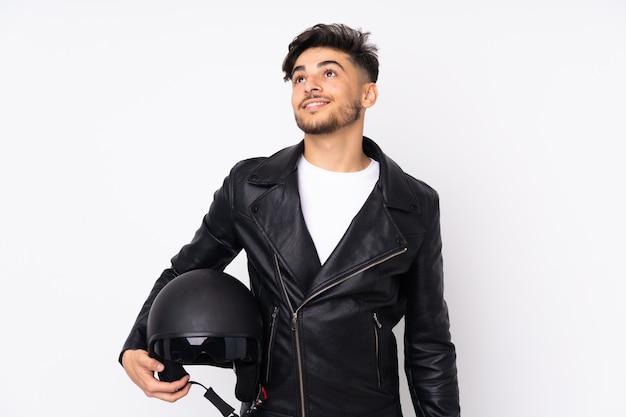 Arabian mężczyzna w kasku motocyklowym na białym tle na białej ścianie patrząc w górę podczas uśmiechu