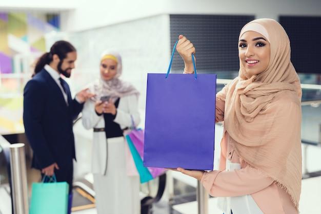 Arabscy ludzie stoi w centrum handlowym z zakupy