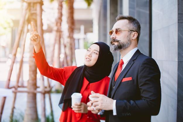 Arabscy muzułmańscy biznesmeni mężczyzna i kobieta rozmawiają razem planując przyszły projekt marzeń razem ręka wskazująca na wysokość