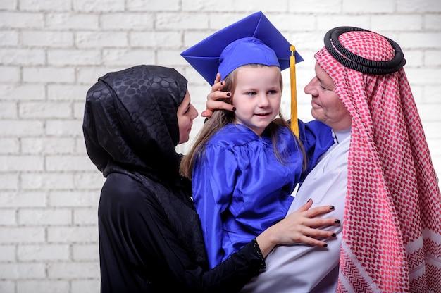 Arabska bliskowschodnia rodzina pozuje z kończyć studia córką na białym tle