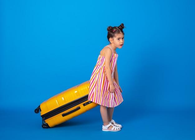 Arabska dziewczynka w kolorowych ubraniach zmęczona noszeniem z żółtą walizką na niebieskiej powierzchni.