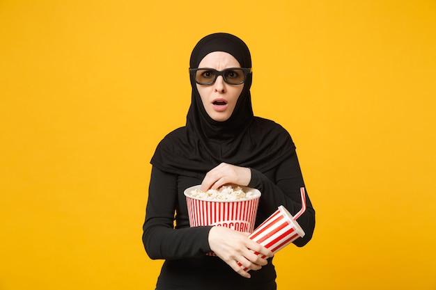 Arabska kobieta muzułmańska w hidżab czarne ubrania 3d okulary imax oglądać film film trzymać popcorn, filiżankę sody na białym tle na żółtą ścianę portret. koncepcja życia ludzi. .