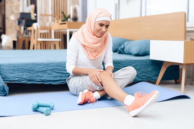 Arabska kobieta robi gimnastyka w sypialni.