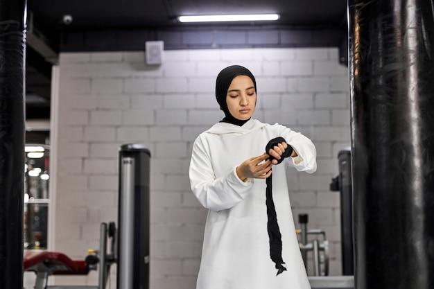 Arabska kobieta w muzułmańskiej odzieży sportowej zawiązuje elastyczne bandaże na rękach. silna suczka przygotowuje się do treningu, sama boksuje. na siłowni