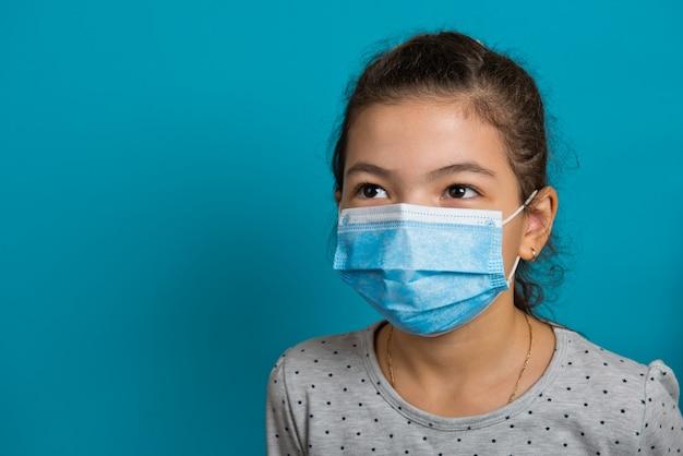 Arabska mała dziewczynka w masce medycznej na niebieskim tle. zbliżenie.