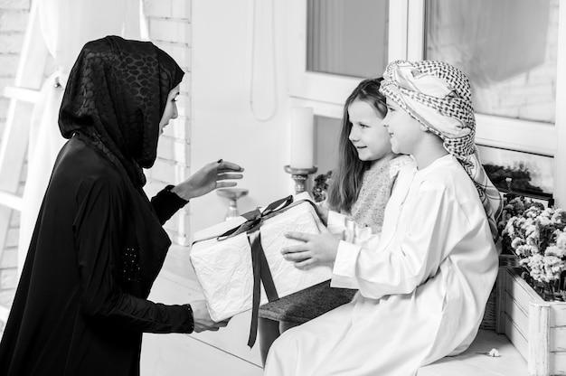 Arabska matka i dzieci pozują z prezentem.