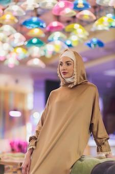 Arabska młoda muzułmanka siedzi w kawiarni.